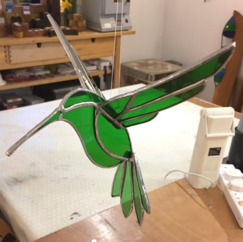 A colourful stained glass hummingbird made on the Vitreus Art workshop