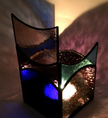 A blue and purple candleholder with 4 sides and a mirrored base