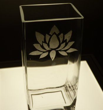 A glass vase etched with a lotus flower design on the Vitreus Art etching class