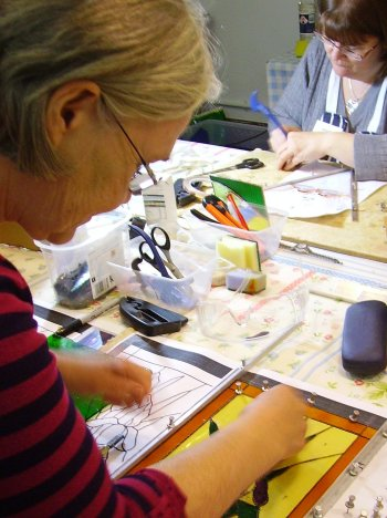 Vitreus Art improvers class working on copper foil stained glass panels