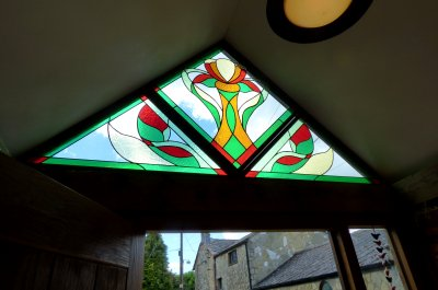 A large triangular porch window created in three sections by Vitreus Art